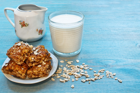 oat snacks, a glass of milk on a blue wooden table