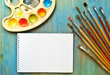 Brushes, palette and sketch pad on blue wooden table Stock Photo