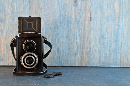 Old retro camera on a blue wooden background Stok Fotoğraf