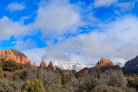 Dramatic view of Sedona, Arizonas vivid red sandstone formations as they rise above the high desert juniper forest.