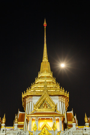 relic: Tower of Buddhist temple in Bangkok with the full moon.