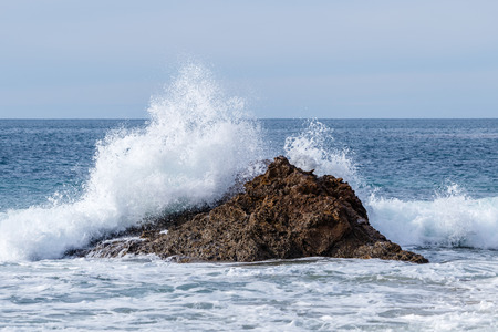 Wave crashing into offshore rock on the California Coast.