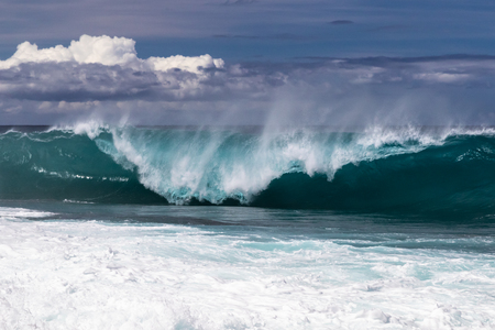 Wave curling on Hawaiian beach, about to crash on the water below. Spray flyng back on waves top. South Point. White sea spray thrown into the air; clouds in the background. On Hawaiis Big Island. 版權商用圖片