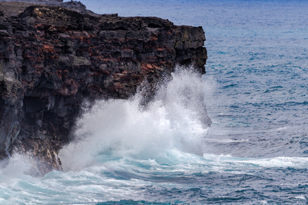 Large waves crashing against tall volcanic cliffs on Hawaiis Big Island, Below Chain of Craters road in Volcano National Park. Pacific ocean in the background. 版權商用圖片