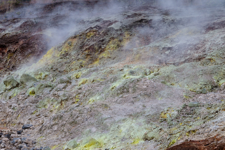 Sulfur Bank in Volcano National Park in Hawaii. Yellow sulfer deposits are on the ground; volcanic gas rise into the air.