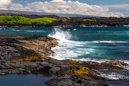 Wave crashing on dark lava rocks of Black Sand Beach (Punaluu), on the Big Island of Hawaii