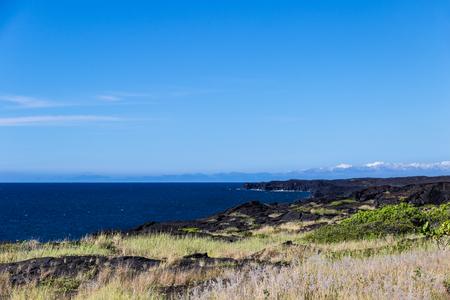 View of rugged coastline on Hawaii's Big Island in Volcano National Park. Black volcanic rocks and vegetation are in the foreground; deep blue Pacific ocean and sky are in the distance.