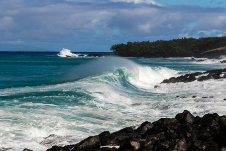 Curling wave cresting and trailing sea spray as it breaks on  the shoreline near South Point on Hawaii's Big Island. Behind it is a rocky strip of land with trees. Storm clouds are overhead.