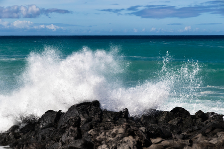 Wave breaking on the western Kona coast of Hawaiis Big Island near South Point. White sea spray thrown into the air; Deep blue-green Pacific ocean, and blue sky with clouds in the background.