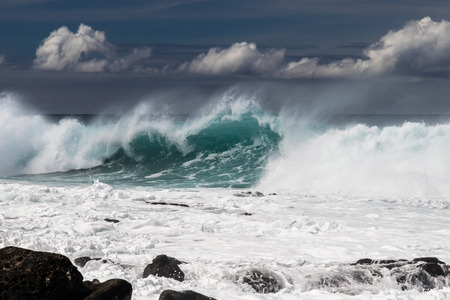Large wave from tropical storm breaking on western Kona coast in Hawaii. White spray and foam on the water. Rocks in foreground. 版權商用圖片