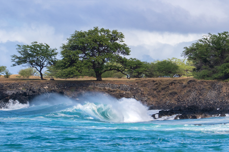 Curling wave cresting and trailing sea spray as it breaks near the shoreline of the Kona coast on Hawaii's Big Island. Behind it is a rocky strip of land with trees. Storm clouds are overhead.
