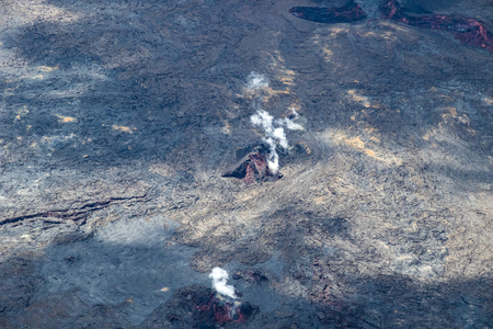 Active fissures in Leilani Estates on Hawaii's Big island. Surrounded by recent lava flow, red magma is visible; white volcanic gas rises from the vents. 写真素材