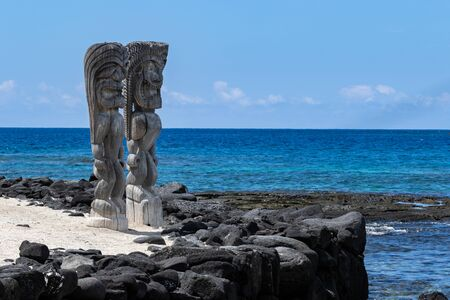 Two Wooden Tikis in the place of refuge (Honaunau) sanctuary, on the Big Island of Hawaii. Standing in white sand with a black lava barrier wall; Pacific ocean and blue sky are in the background. Banque d'images