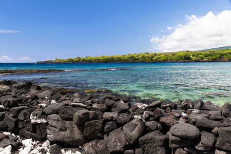 View of kealakekua bay on Hawaiis Big Island, looking from Puuhonua Historical Park. Crystal blue-green water in the bay; coastline in the background, black Volcanic rock in foreground.