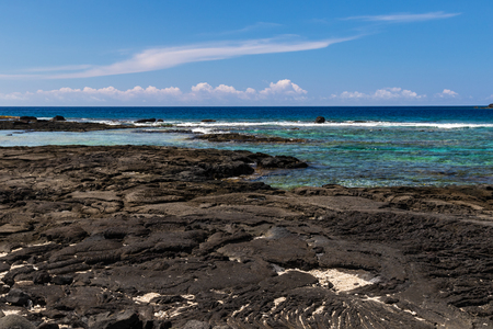 View of Blue Pacific ocean from Puuhonua o Honaunau Historical Park, Big Island, Hawaii. Crystal blue-green water in the bay; coastline in the background, volcanic rock and sand in foreground.