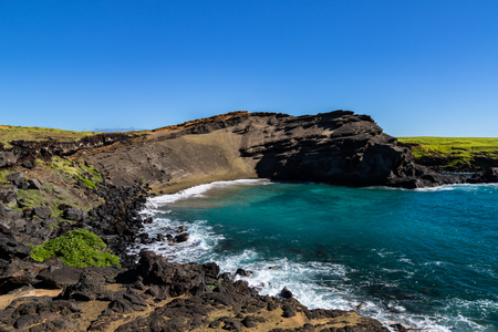 Green sand beach (papakolea) near South Point on Hawaiis Big Island. Beach is at the bottom of the steep slope; blue-green ocean, rocky shoreline is in the foreground. 版權商用圖片