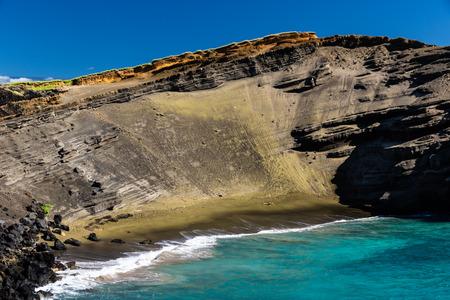Green sand beach (papakolea) near South Point on Hawaii's Big Island. Steep slope of old volcano cone is behind the beach; blue-green ocean & deep blue sky. 写真素材