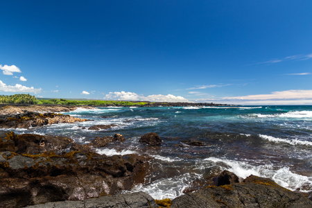 Ocean view at Black Sand Beach on Hawaii's Big Island. Blue pacific ocean with waves, rough volcanic rock and brown vegetation on shore. Coastline with green plants in the distance.
