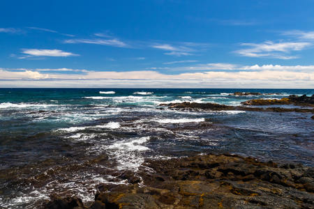 Rocky shoreline at Black Sand Beach (Punaluu), on the Big Island of Hawaii. Blue Pacific ocean washing against volcanic rocky shore; Blue sky with clouds in the distance. 版權商用圖片
