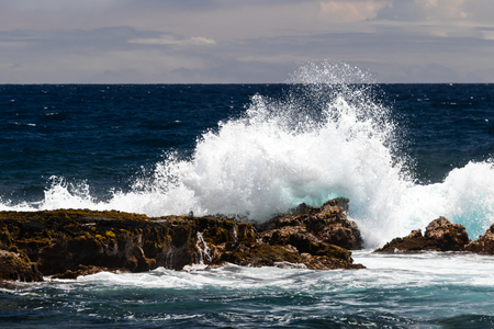 Wave crashing into a volcanic rock just offshore Black Sand Beach (Punaluu), Big Island of Hawaii. White sea in the air; deep blue Pacific ocean and clouds are in the background. 版權商用圖片