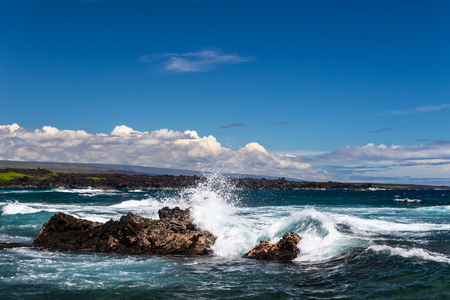 Wave crashing on volcanic rock at Black Sand Beach (Punaluuu), on the Big Island of Hawaii. White spray rises in the air; deep blue Pacific ocean, sky clouds are in the background. 版權商用圖片