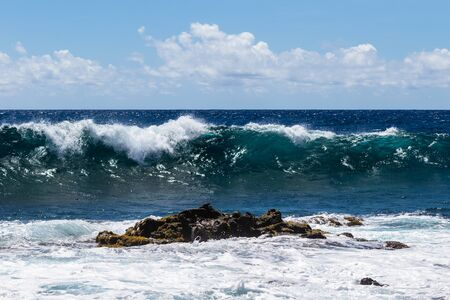 Wave breaking near shore on South Point, on Hawaii's Big Island. Volcanic rock in foreground. Foam on top of wave's clear blue-green water; deep blue Pacific ocean in the background.