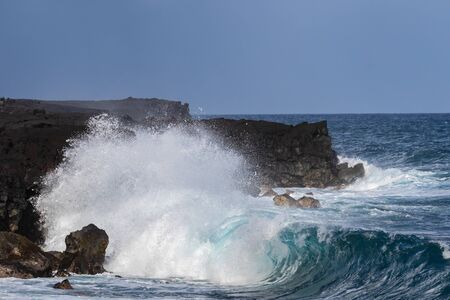 Curling wave at black sand beach, western coast of Hawaii's Big Island. Spray in the air, volcanic cliffs in the background.