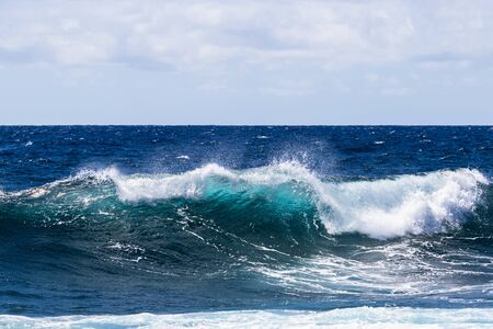 Wave breaking near shore on South Point, on Hawaii's Big Island. Foam on top of wave's clear blue-green water; deep blue Pacific ocean in the background.