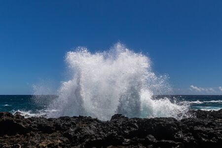 Wave breaking on the rocky coastline of Hawaii's Big Island near South Point. White sea spray thrown into the air; Deep blue Pacific ocean, and blue sky with clouds in the background.