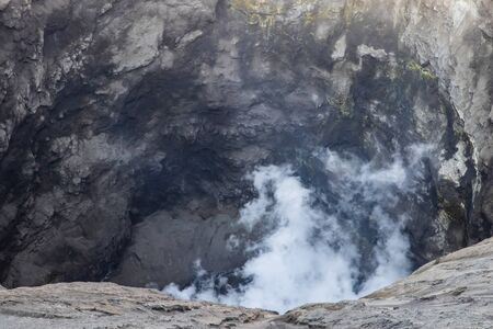 Closeup of interior of Mount Bromo crater, East Java, Indonesia. White gas rising; sulfur visible on rock face in back.