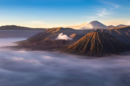 Mount Bromo volcano at sunrise; Island of East Java, Indonesia. Clouds cover the valley floor; Luhur Poten Temple at the foot of the cone. Gas from another volcano in the background rising against the blue sky. Фото со стока