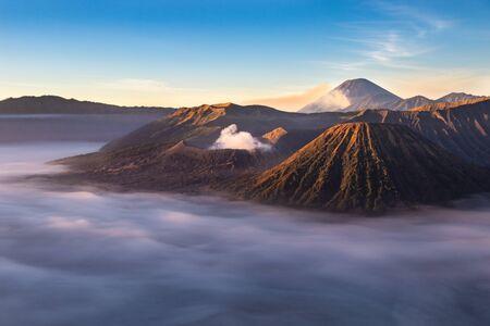 Mount Bromo Vulkan bei Sonnenaufgang; Insel Ost-Java, Indonesien. Wolken bedecken den Talboden; Luhur Poten Tempel am Fuße des Kegels. Gas von einem anderen Vulkan im Hintergrund steigt gegen den blauen Himmel auf. Standard-Bild