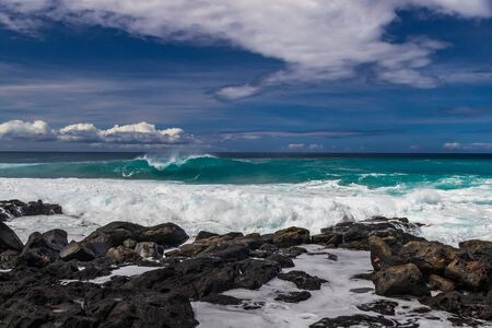 Shoreline of volcanic rocks on Hawaiis Big Island; foam and surf in foreground. Curling wave breaking offshore; in the background is the Pacific ocean, with blue skies and clouds overhead.