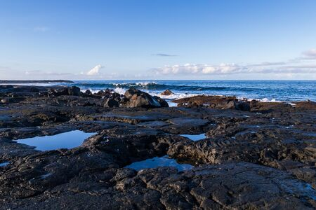 Rocky volcanic shoreline at low tide, near Kona, on Hawaii's Big Island. Seawater fills cavities in the stones. Wave breaking offshore; Blue sky and clouds overhead.