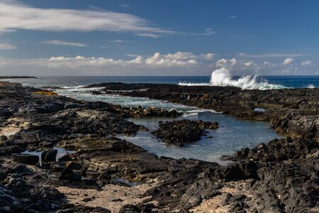 Tidepool at volcanic beach near Kona, on Hawaii's Big Island. Black rocks in foreground, with waves from incoming tide. Blue ocean, sky and clouds in the distance.