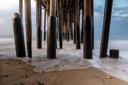 Closeup of pillars, Ventura Pier, Ventura, California. Early light from sunrise visible from left. sand and rocks in foreground; smooth incoming wave reaching shore; ocean, sky beyond.