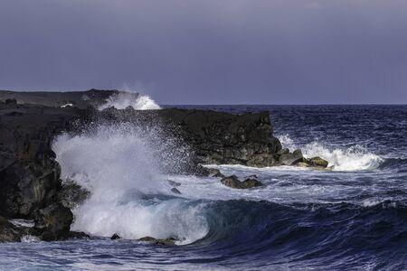 Wave crashing on black volcanic cliffs, black sand beach on Hawaii's Big Island. Ocean and blue sky in background.