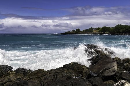 Wave breaking on rough shore of the Kona coast, on Hawaii's Big Island. Blue-green Pacific ocean beyond; rocky shoreline with trees in the distance. Cloudy blue sky above.