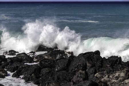 White wave breaking against black volcanic rocks  on the Kona coast of Hawaii's Big Island. Vivid blue-green pacific ocean in the distance.