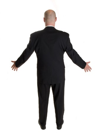 Stock photo of the back side of a well dressed businessman holding his arms out to his sides in a welcoming gesture, or a request to rise, or dismay.  Full length, isolated white. photo