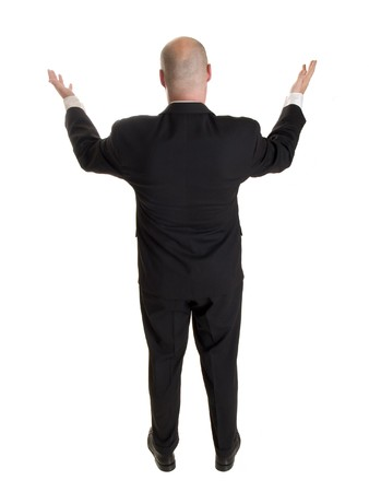 Stock photo of the back side of a well dressed businessman holding his arms up in a gesture as if addressing a crowd or requesting a congregation to rise. Stockfoto
