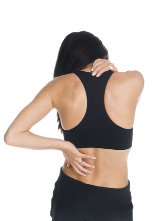 back ache: Isolated studio shot of a woman in a fitness outfit experiencing neck, shoulder  and back pain. Stock Photo