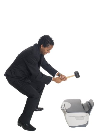 Isolated studio shot of a businessman swinging a mallet to smash his printer.