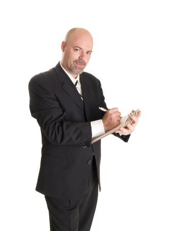making notes: Stock photo of a well dressed businessman making notes on a clipboard, isolated on white.