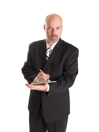 Stock photo of a well dressed businessman making notes on a clipboard, isolated on white.