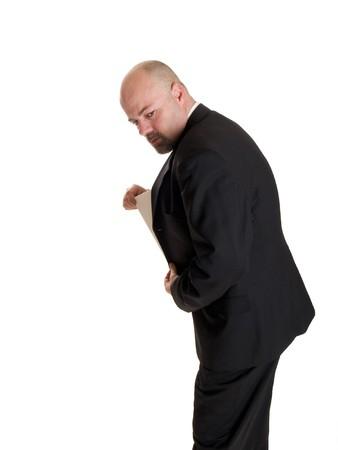 deceptive: Stock foto van een zaken man verbergen een geheim document in zijn jas zak.