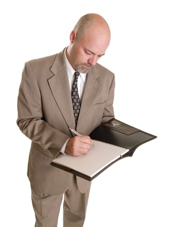 Stock photo of a well dressed businessman taking notes in a notebook, isolated on a white background. photo
