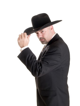 tipping: Stock photo of a well dressed businessman tipping his cowboy hat, isolated on white.