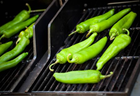 roasting: Green Hatch chiles roasting on the grill. Stock Photo