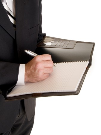 Stock photo of a well dressed businessman taking notes in a notebook. photo